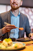 Man eating sushi using chopsticks on business lunch
