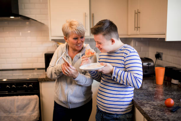 Eating Toast in the Kitchen A boy with down syndrome eats toast whilst his mother shows him her smartphone. real life stock pictures, royalty-free photos & images