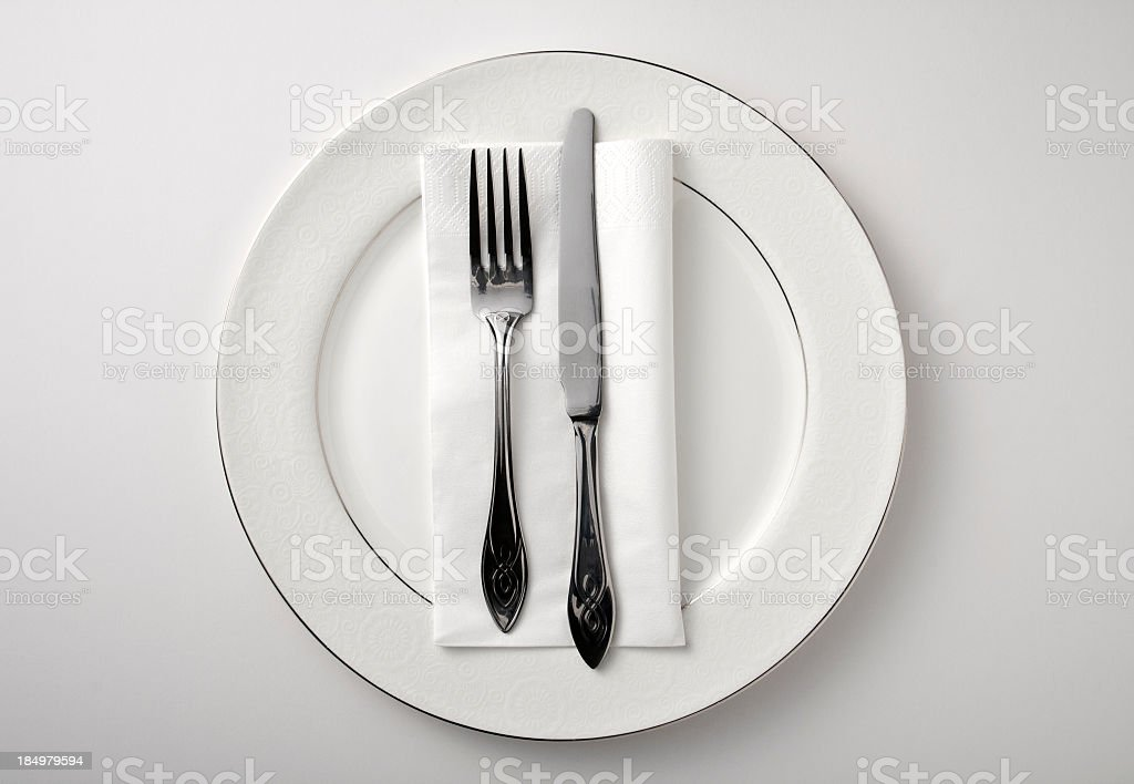 Eating utensils on a white plate against a white background stock photo