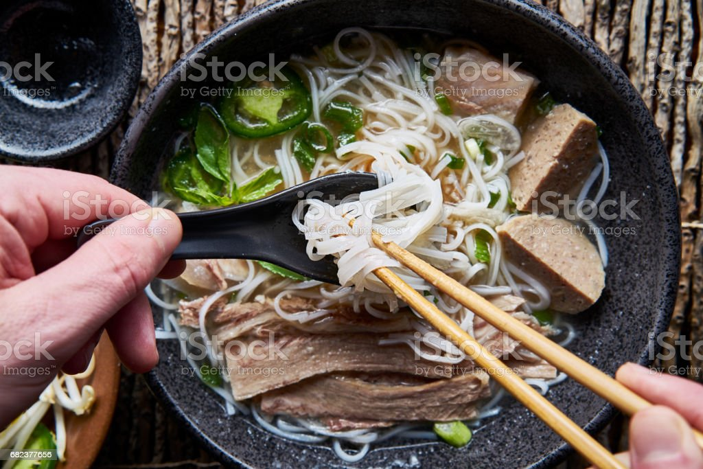 eating vietnamese pho with chopsticks and spoon stock photo