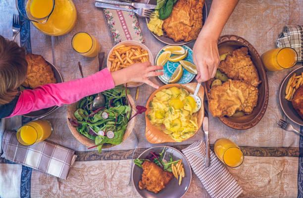 wiener schnitzel mit kartoffeln und grünem salat essen - österreichische kultur stock-fotos und bilder