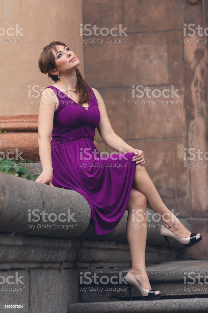 eautiful woman in purple dress sitting on the steps. People royalty-free stock photo