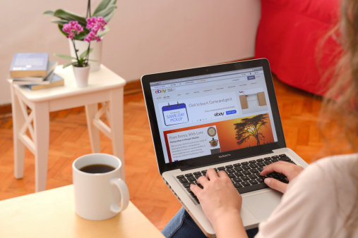 İstanbul, Turkey - November 12, 2013: Woman using MacBook Pro displaying eBay homepage. MacBook, the tablet computer produced by Apple Computer, Inc. eBay is an online shopping website.