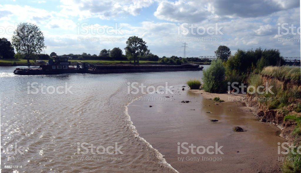 Ebb and flow made by towboat stock photo