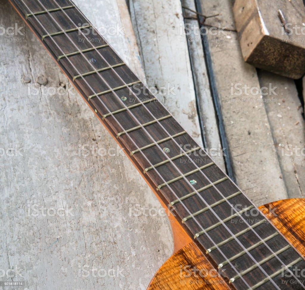 Ebony finger board of curly koa ukulele gloss finished against wooden background. Selective focus stock photo