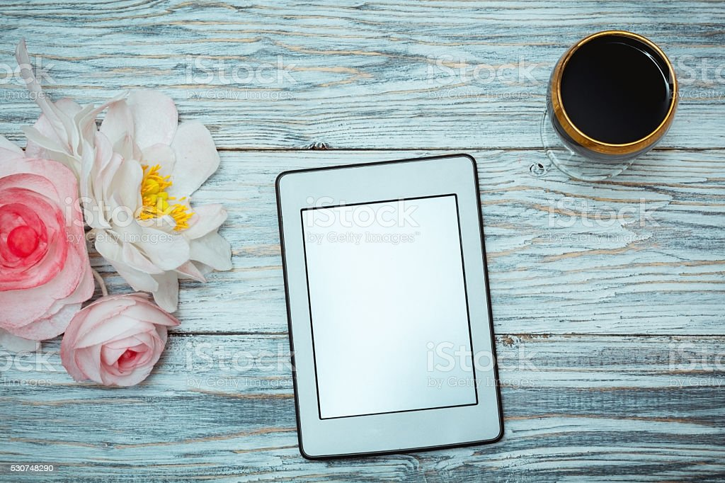 ebook and glass of red wine and flowers stock photo