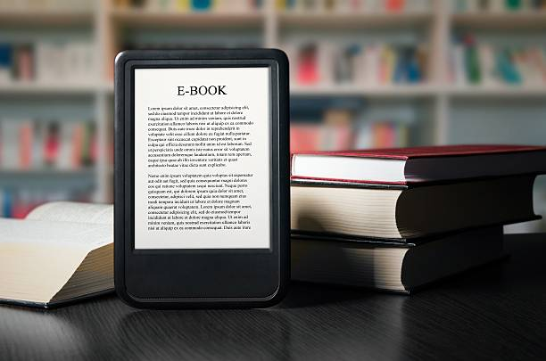 E-book reader device on desk in library stock photo
