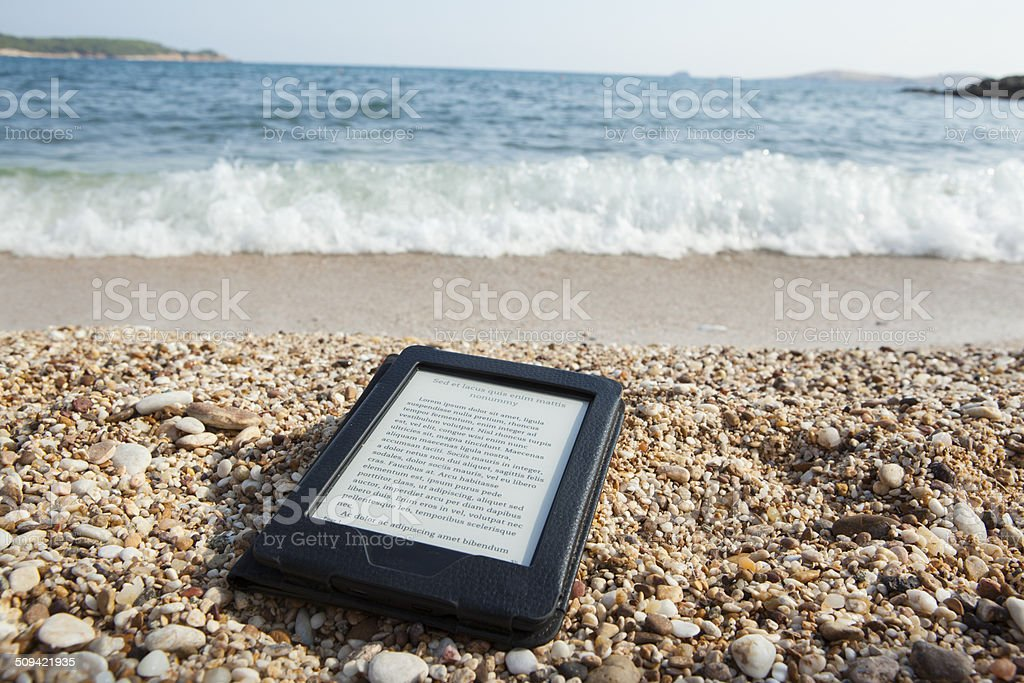 e-book reader on a beach with LOREM IPSUM text necessities for reading pleasure on sea side Beach Stock Photo