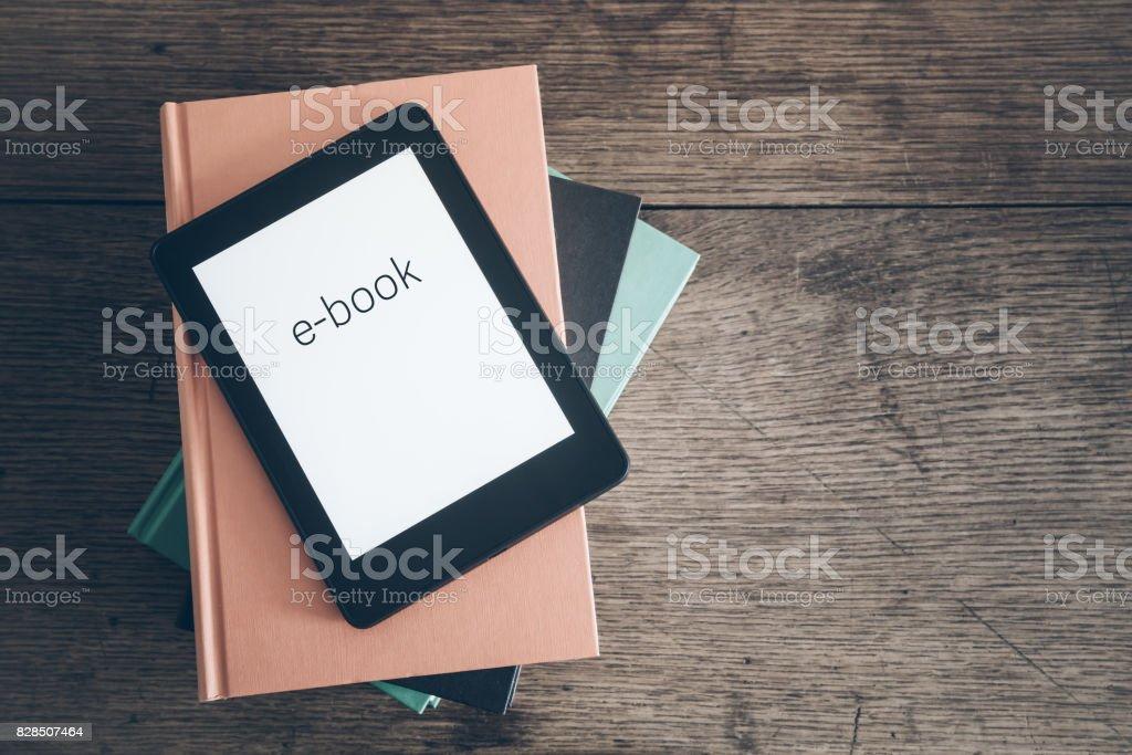leitor de e-book sobre uma pilha de livros sobre o conceito de mesa de madeira rústica - Foto de stock de Alemanha royalty-free
