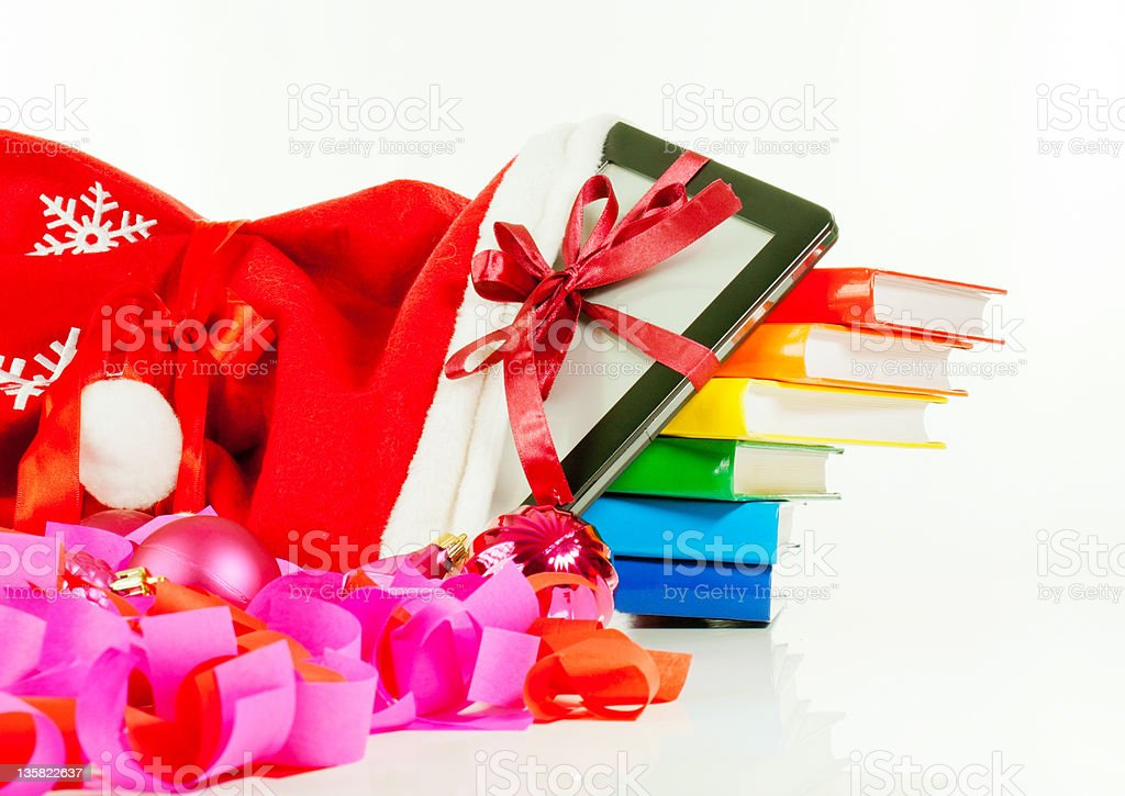 E-book reader with stack of books in bag stock photo