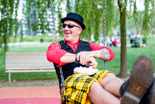 eccentric and crazy man playing on a children's swing, man wearing sunglasses and bowler hat in a playful pose, original clothing with red shirt, waistcoat with pins and Scottish kilt