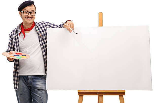 Eccentric artist posing next to a canvas stock photo