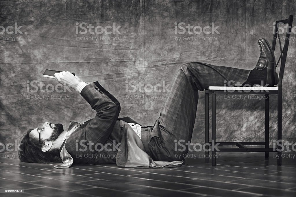 Eccentric businessman reading a book while lying on the floor stock photo