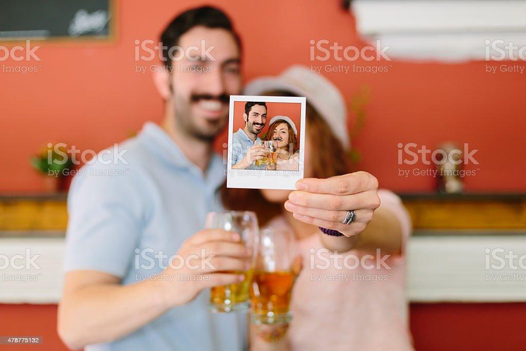 Excêntrico casal segurando uma foto polaroid - foto de acervo