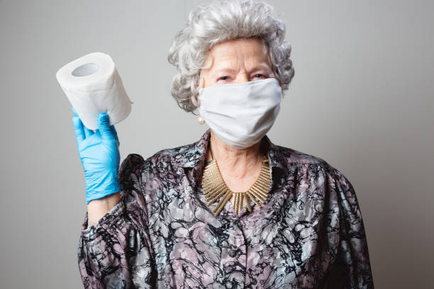 eccentric happy senior woman holding with face mask and protective gloves holding a roll of toilet paper stock photo