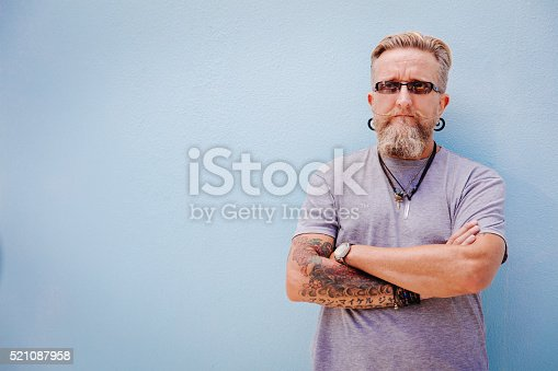 istock Eccentric mature man with tattoo and earrings 521087958