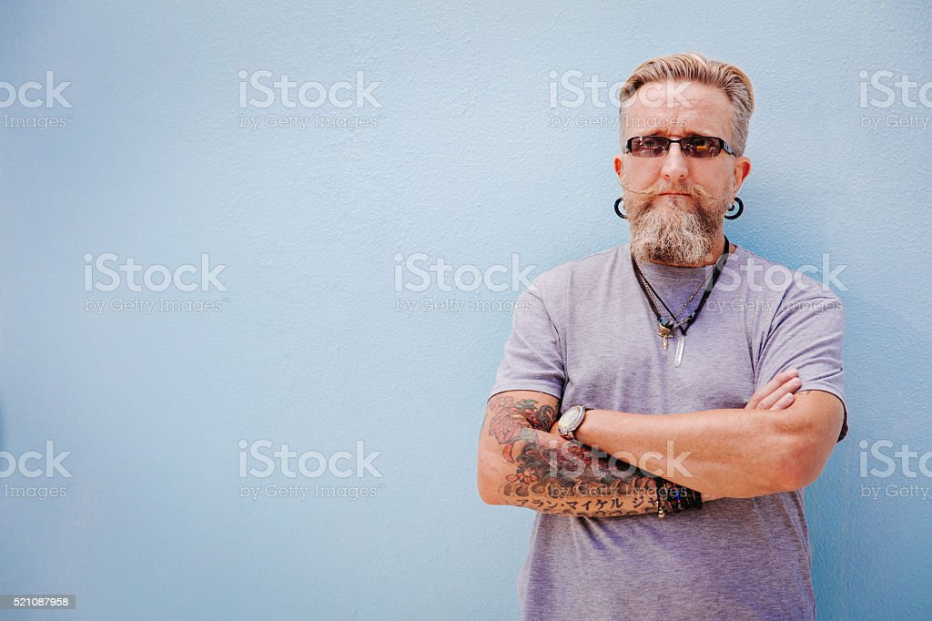 Eccentric mature man with tattoo and earrings stock photo