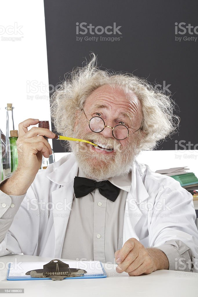 Eccentric scientist in lab thinks of ideas Eccentric senior scientist in lab holds pipe, thinks of ideas. Blank blackboard in background. HIgh key, vertical, copy space. Active Seniors Stock Photo