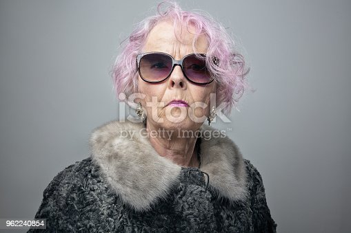 Senior woman with pink hair wearing old fashioned fur coat and sunglasses, looking at camera with arogant expression
