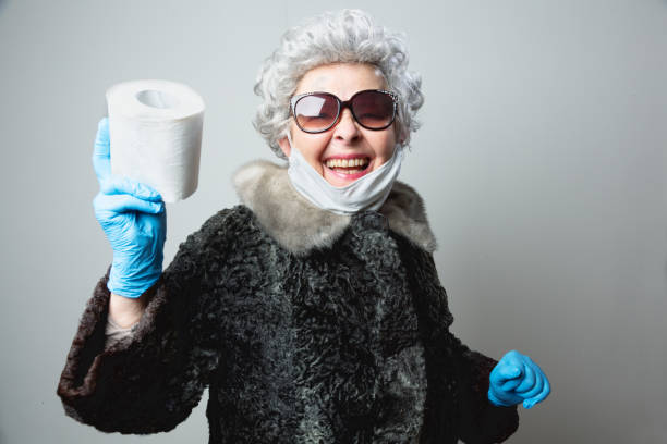 eccentric senior woman happy with a roll of toilet paper during coronavirus crisis stock photo