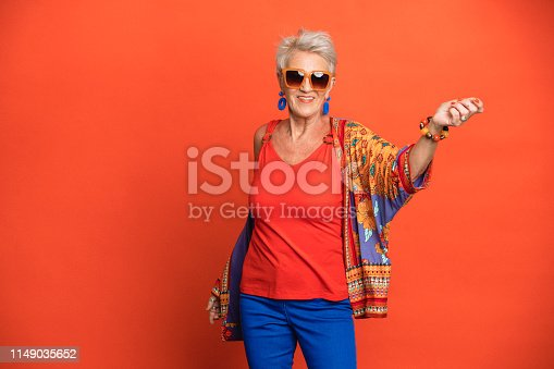 Portrait of a smiling senior woman standing in front of an orange background dressed in bright clothing with sunglasses on. Her arms are outstretched and she looks like she's dancing.