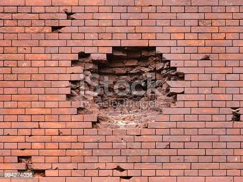 istock Echoes of war. Wall damaged by a military projectile (bomb), broken red brickwork. Brest fortress, exterior, fortification 994274036
