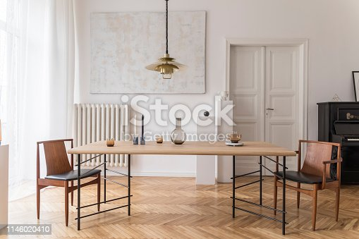 Stylish and modern dining room interior with design furniture. Eclectic decor.