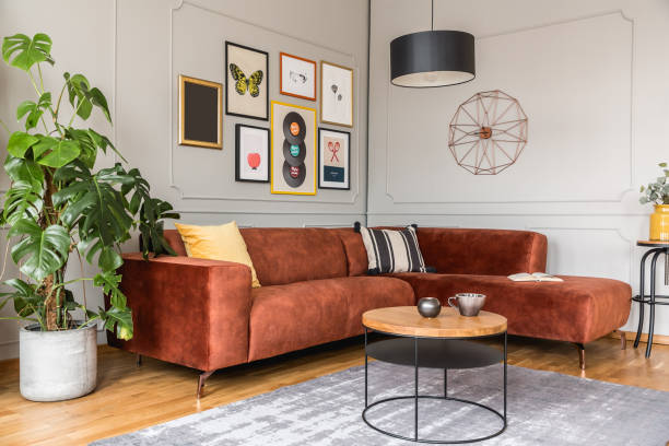 Eclectic living room interior with comfortable velvet corner sofa with pillows stock photo