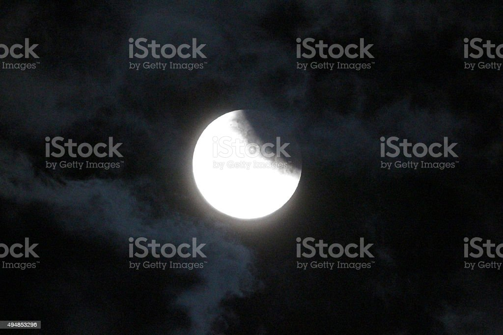 Eclipse and cloud wisps stock photo