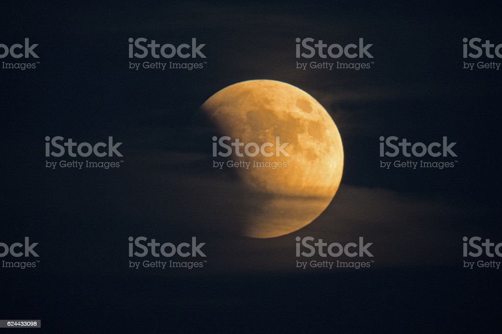 Eclipsing Moon Sits in Misty Clouds stock photo