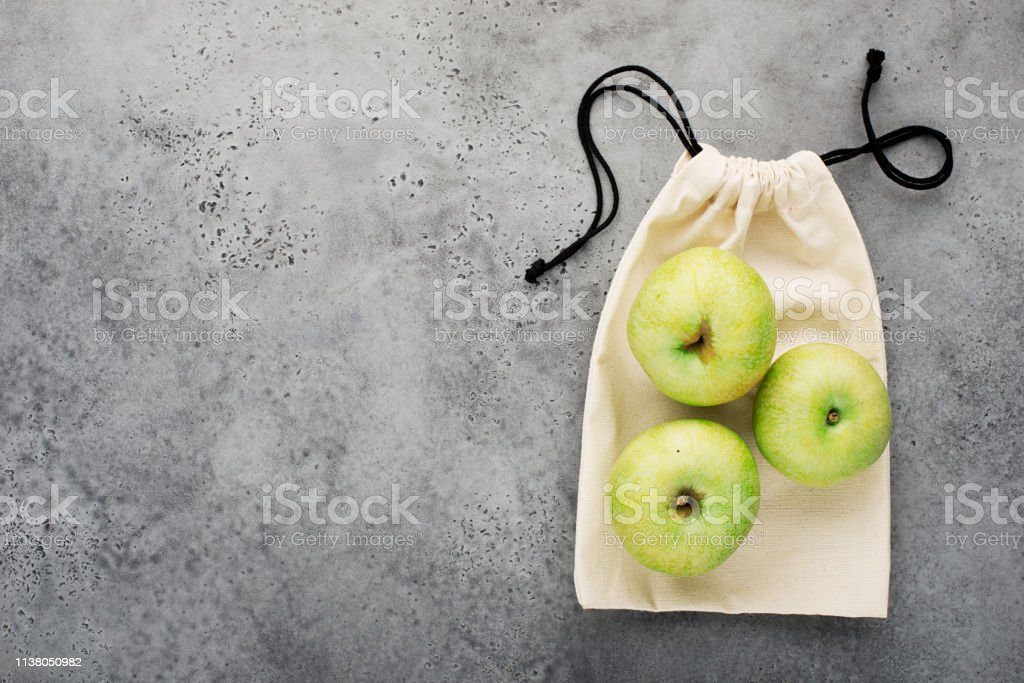 Eco bag for products. Apples on the background of a linen bag on a...