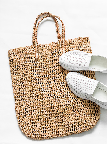 Eco bag made of straw, sport white snickers shoes on a white background, top view. Shopping walking concept