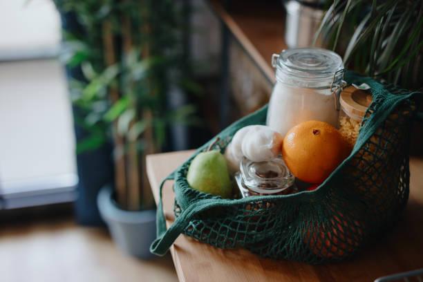 Eco-Tasche auf Küchentheke mit Lebensmitteln in Gläsern und frischem Obst. Null-Abfall-Konzept – Foto