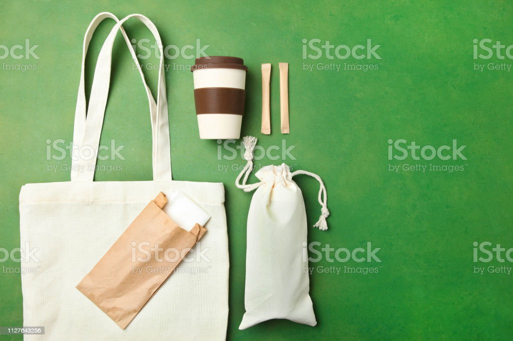 Eco bag, reusable bamboo cup and craft packages on green background....