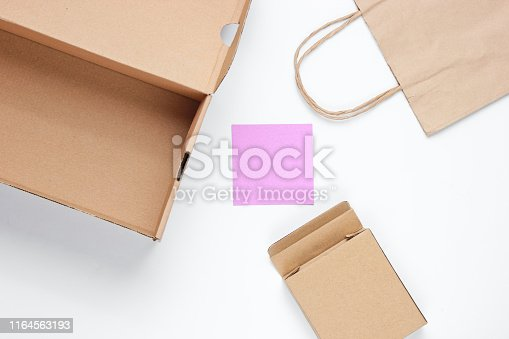 Eco concept. Cardboard boxes, paper bag, memo sheet on white background. Top view