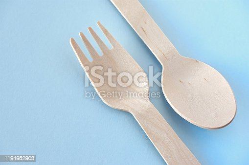 Eco cutlery from pine wood. Disposable tableware from natural materials. Wooden spoon and fork on a pastel blue background. Image with copy space. Zero waste, plastic free, stop pollution concept.