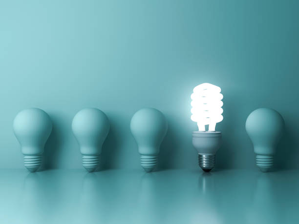 eco energy saving light bulb , one glowing compact fluorescent lightbulb standing out from unlit incandescent bulbs reflection on green background - efficiency stock photos and pictures