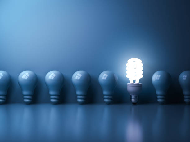 Eco energy saving light bulb , One glowing compact fluorescent lightbulb standing out from unlit incandescent bulbs reflection on blue background , individuality and different concept stock photo