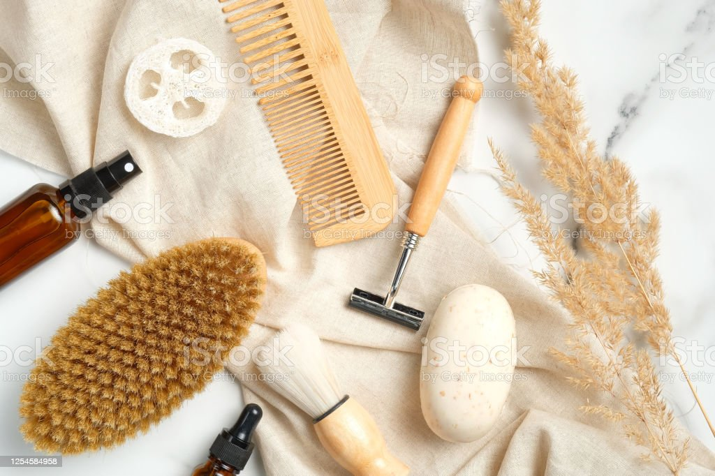 Eco Friendly Bathroom Accessories For Man On Marble Background With Beige Fabric And Dry Flowers Flat Lay Shaving Brush Razor Body Brush Cosmetic Bottle Homemade Soap Loofah Wooden Hair Comb Stock Photo