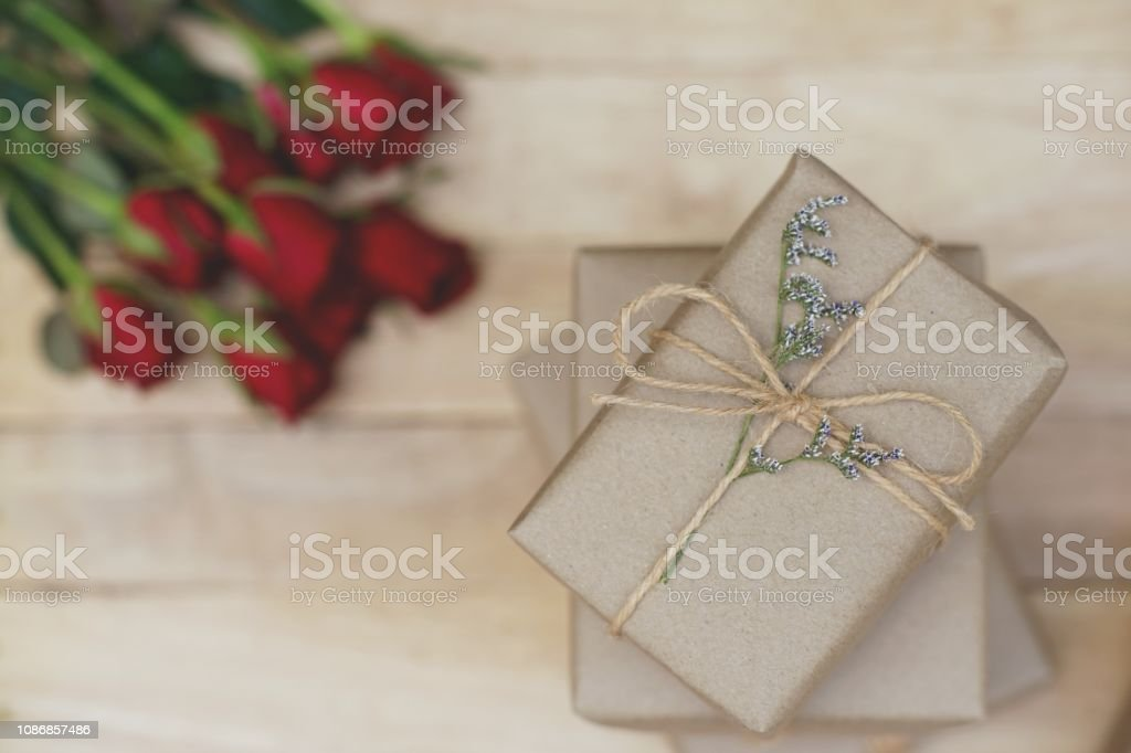 Eco friendly brown paper wrapped gift box present decorated with rose...