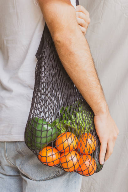Eco friendly lifestyle and healthy diet concept. Detail of a Man standing sideways and holding reusable mesh cotton shopping bag with fresh and eco vegetables. stock photo