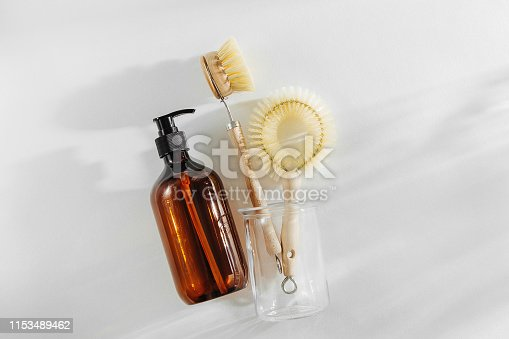 1169442284 istock photo Eco friendly natural cleaning tools and products, bamboo dish brushes and soap dispenser on white background. Zero waste concept. Plastic free. Flat lay, top view 1153489462