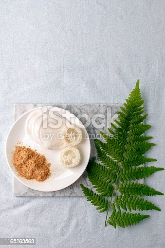 istock Eco friendly products for home cleaning, zero waste lifestyle, flat lay on white background. Mustard and natural luffa sponge on white plate and branch of fern 1165263563