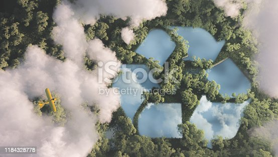 istock Eco friendly waste management concept. Recyclyling sign in a lake shape in the middle of dense amazonian rainforest vegetation viewed from high above clouds with small yellow airplane. 3d rendering. 1184328778