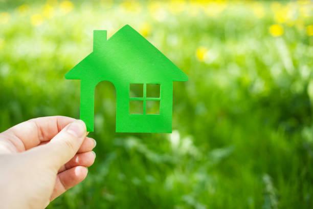 Öko-Haus-Konzept, Hand hält grüne Öko-Haus-Ikone in der Natur – Foto