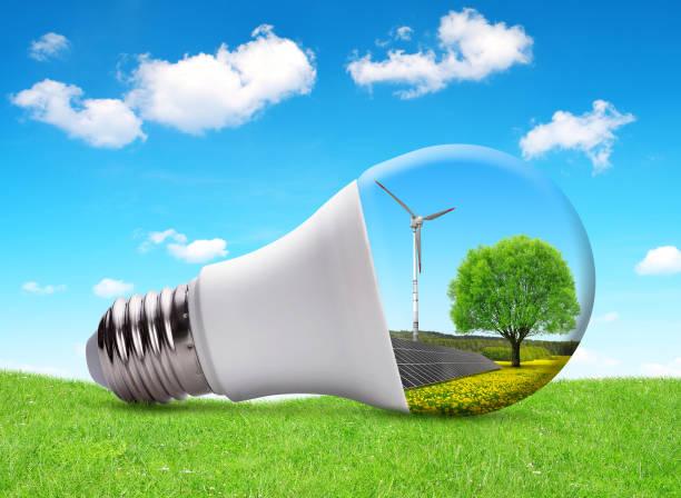 Eco LED light bulb with solar panel and wind turbine. stock photo