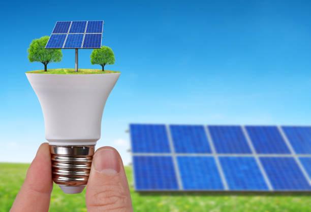 eco-led glühbirne mit solarzellen in der hand. - solarleuchten stock-fotos und bilder