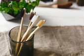 istock eco natural bamboo toothbrushes in glass on rustic background with greenery. sustainable lifestyle concept. zero waste home. bathroom essentials, plastic free items 1030491550