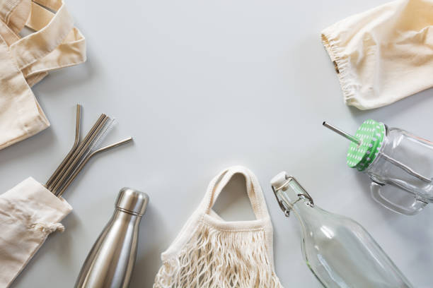 eco natural metallic straws, cotton bag, glass and metal bottle on grey. sustainable lifestyle concept. zero waste, plastic free. pollution environment. - circular economy imagens e fotografias de stock