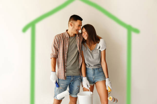 Eco paint for painting wall. Young couple with paint rollers embracing and smiling after painting wall in new home stock photo